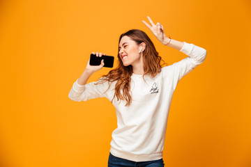 Emotional young woman listening music using mobile phone dancing.