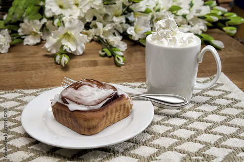 Fotobehang Chocolade Morning breakfast snack with hot chocolate in large white mug loaded with whipped cream and large cinnamon danish. Flowers on table.