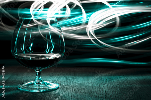 A glass of cognac on bright background light effect.