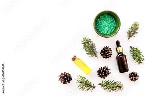 Pine spa cosmetics, products for skin care. Fir essential oil and green aromatic spa salt near branches and cones on white background top view copy space © 9dreamstudio