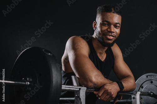 Wall mural muscular young african american sportsman leaning at barbell and smiling at camera on black