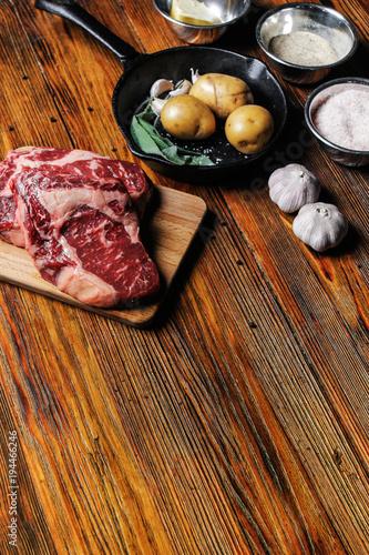 Aluminium Steakhouse Ribeye steak, garnish and seasoning, ingredients on a rustic wooden table