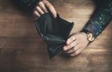 Hands showing empty wallet.