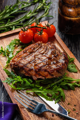 Plexiglas Steakhouse Grilled beef steak on wooden cutting board.