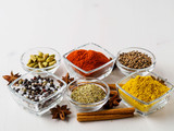 spice set-coriander, red pepper, turmeric, cinnamon, star anise, rosemary various seasonings in glass cups, on white wooden table, side view, blank space for text. - 194476607