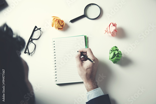 businessman hand notepad with idea on table
