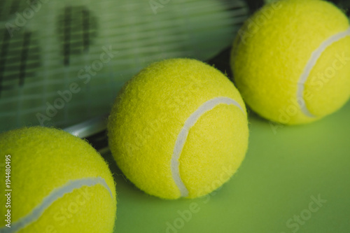 Fotobehang Tennis Macro view of three tennis balls and a tennis racket on green background.
