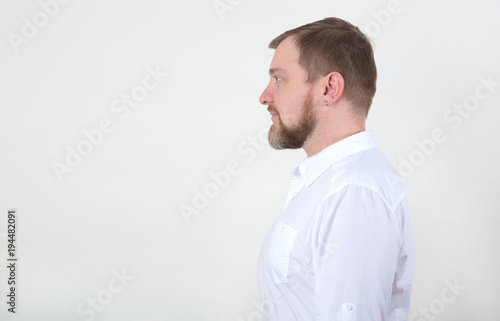 Side view male. Portrait in the profile of bearded man in white shirt looking on copy space.