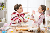mother and daughter make dough for buns and play with flour, home kitchen interior, healthy food concept - 194486696