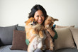 Happy Woman Holding Yorkie and Spitz Dogs on Sofa