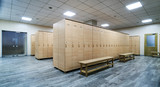 Interior of a locker room. Clean empty dressing room with big lockers and wooden bench - 194503219