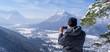 Mann genießt die Aussicht und schaut herab auf Garmisch-Partenkirchen und Farchant und macht Fotos mit seinem Smartphone