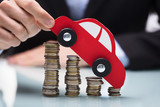 Businessman Holding Red Car Over Stacked Coins