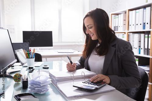 Happy Businesswoman Calculating Bill