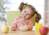 Funny child eating healthy food with a spoon at home - 194546014
