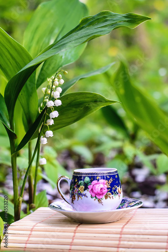 Fotobehang Lelietjes van dalen Beautiful fairy picture with a cup of tea and lilies of the valley