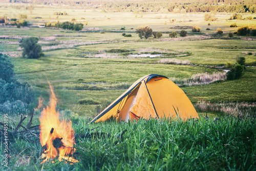Fotobehang Pistache Orange tent with fire in field with green grass