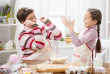 mother and daughter make dough for buns and play with flour, home kitchen interior, healthy food concept - 194560681