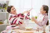 mother and daughter make dough for buns and play with flour, home kitchen interior, healthy food concept - 194560693