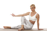 Yoga, sport, training and lifestyle concept - Young blonde woman relaxes while exercising yoga Portrait of young beautiful woman in white sportswear in relax pose.