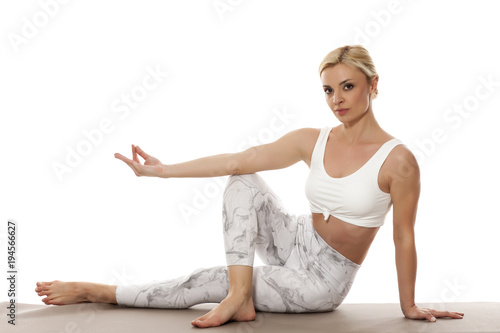 Fototapeta Yoga, sport, training and lifestyle concept - Young blonde woman relaxes while exercising yoga Portrait of young beautiful woman in white sportswear in relax pose.