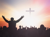 Silhouette people raising hands over blurred the cross on beautiful golden autumn sky sunset background