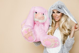 Beautiful sexy blonde woman wearing a pajama, a bunny costume, smiling happily. Fashion model on a beige background in  Easter bunny costume. - 194580659