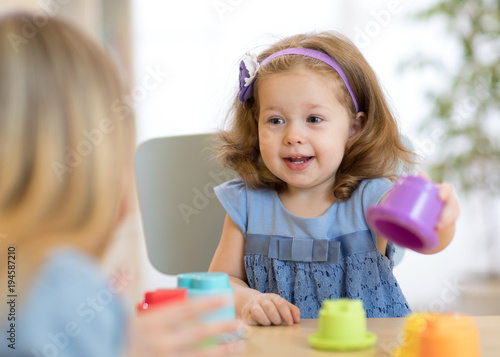 2 year-old child playing with educational cup toys at home.