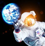 Astronaut in space with raised hand and earth in background - 194592679