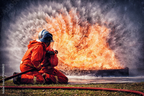 Leinwandbild Motiv Firefighter in fire fighting suit spraying water, Firemen fighting  raging fire with huge flames of burning, Fire prevention and extinguishing concept