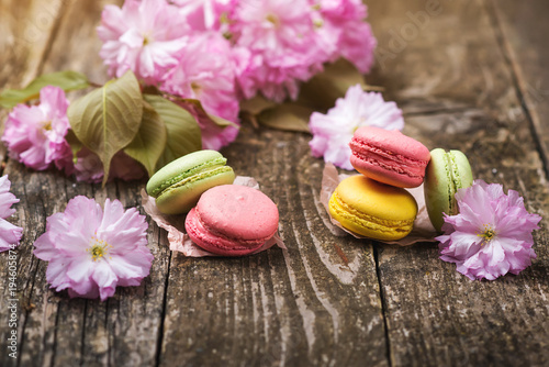 Pink sakura flowers with delisious macarons on dark wooden background , copy space, selective focus Poster