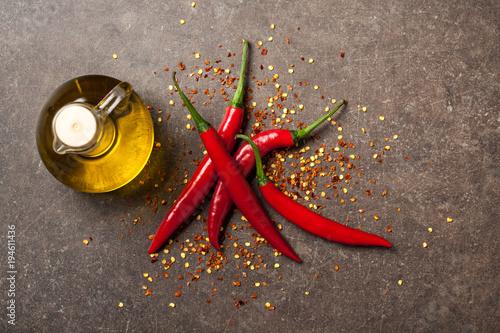 Plexiglas Hot chili peppers Red chili pepper and pitcher of oil on stone background