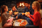 Smiling parents and children eating pizza on the floor - 194618488