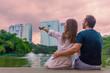 молодая пара мужчина и женщина сидят на берегу озера на фоне небоскребов и розового заката. а женщина указывает пальцем вдаль и пара смотрит на город