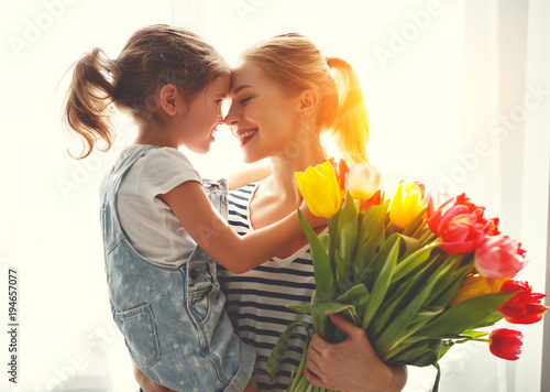 happy mother's day! child daughter   gives mother a bouquet of flowers to tulips.