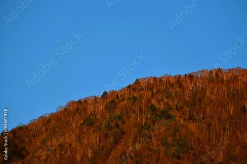 Fotobehang Blauwe jeans 夕日に染まる山