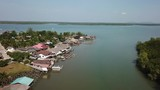 Aerial footage fishing village in Thailand. Traditional fishing boats and aquaculture shrimp farms - 194680818