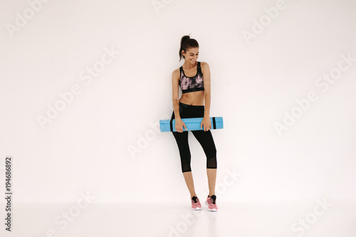 Sportswoman with yoga mat in fitness studio