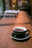 Hot coffee cup on wooden table with books background in vintage tone - 194689275
