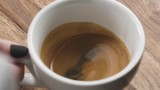 Slow motion handheld shot of swirl espresso in cappuccino cup from above - 194696089