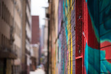 Fototapeta Teenage - An abstract view of an inner city allyway  in Johannesburg, brightly decorated with colourful graffiti, focussed on the foreground and blurred in the distance © Jennifer
