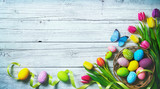 Easter background. Colorful spring tulips with butterflies and painted eggs