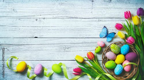 Easter background. Colorful spring tulips with butterflies and painted eggs - 194706072