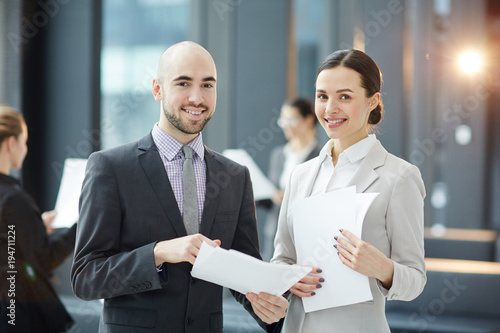 Two young smiling brokers with contracts looking at camera during negotiation