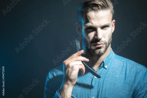 Handsome bearded hairdresser in stylish clothes holding a dangerous razor. Handsome bearded man, hipster with beard and moustache ready for shave. Copy space to advertise barbershop.