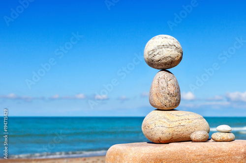 Foto op Canvas Zen White stones balance on a background of blue sky and sea