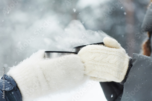 Two friends in white fluffy knitted mittens clinking with cups with hot drinks on snowy winter day outdoors