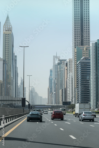 Tuinposter Dubai Cars on the high road in the city. Big modern buildings from both sides