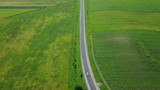 Road among green fields in Cherkessk, Karachaevo-Cherkessia. Beautiful view from above, shooting from a quadopter, 4K - 194739837
