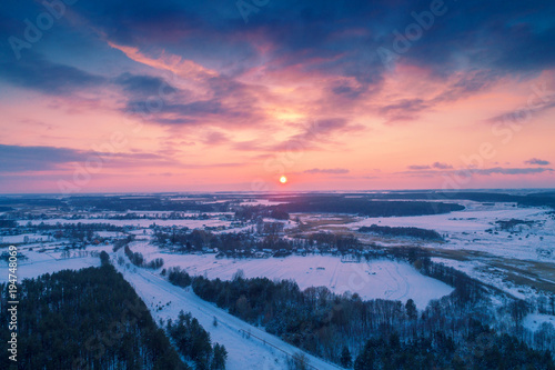Fotobehang Nachtblauw Aerial evening view at countryside and snowy fields during sunset